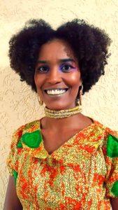 Mulher negra, sorrindo, de cabelos curtos e olhando para a câmera. Cibele Mateus usa uma roupa em tons de laranja e detalhes verdes.