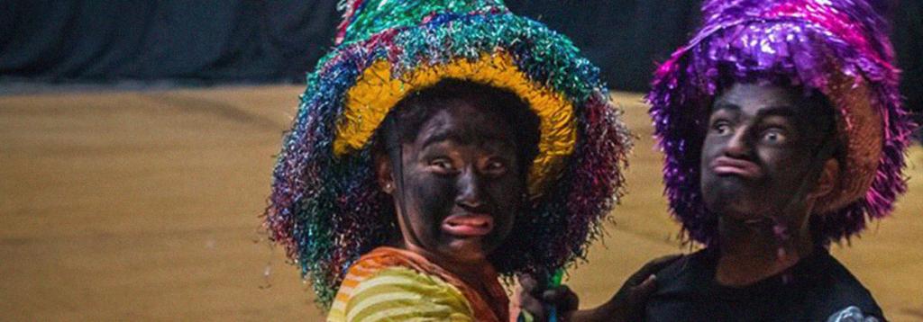 Na imagem, duas pessoas com rostos pintados de preto e chapéus coloridos.