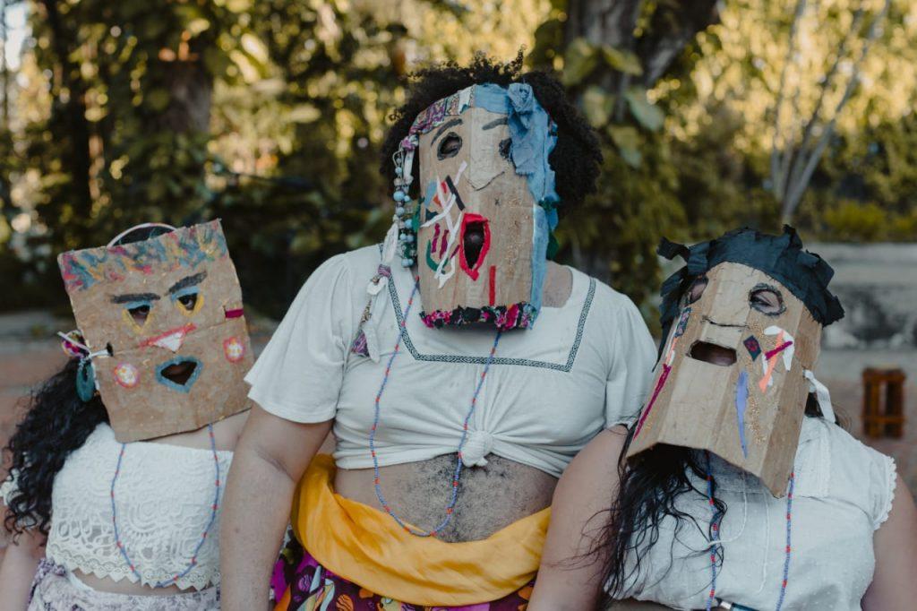 Três artistas do Coletivo Yabá usam máscaras de papelão coloridas com tinta sobre o rosto